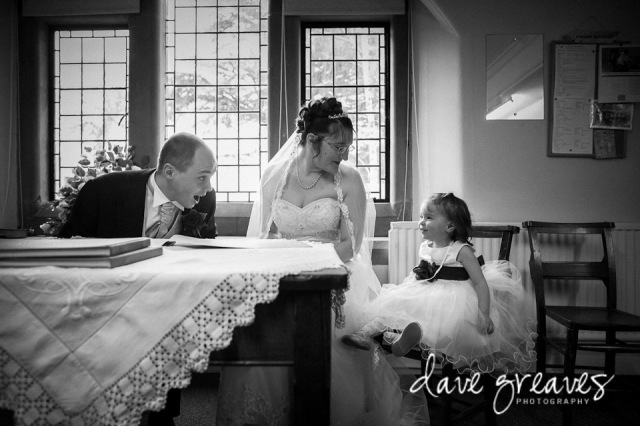 Bride and Groom signing the register shar a joke with the flower girl