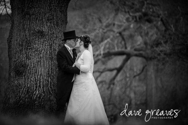 Bride and Groom embrace standing under a tree