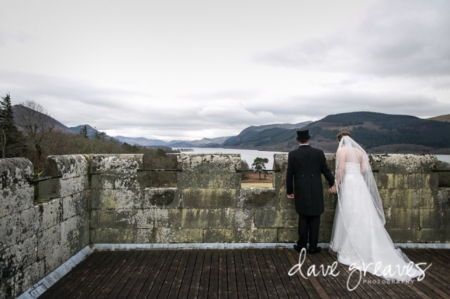 Bride and Groom on the roof of Armathwaite Hall looking at the view across Bassenthwaite Lake