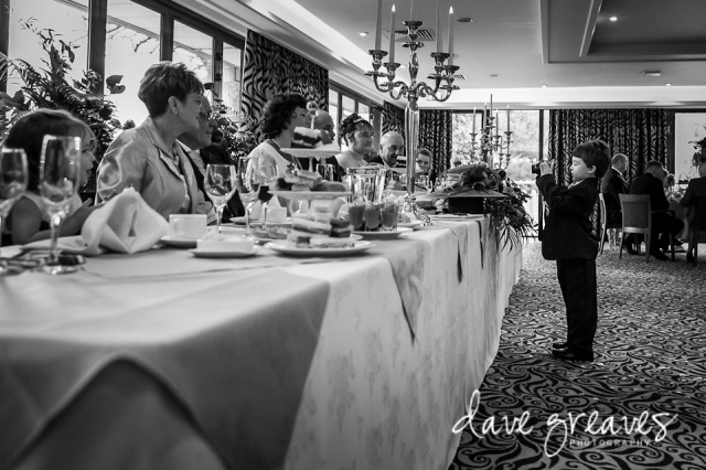 Young wedding guest takes a picture of the top table at wedding reception