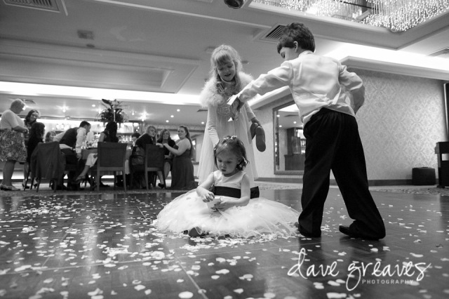 Young guests shower confetti over flower girl