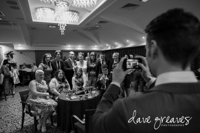 Wedding guest takes a picture of bride and friends