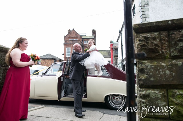 Flower girl being lifted out of wedding car in Wigton