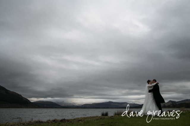 Bride and Groom standing on the shores of Bassenthwaite Lake, Cumbria
